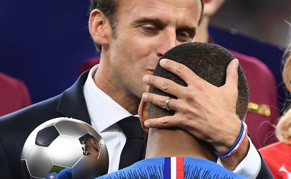 Macron besando a Mbappé.