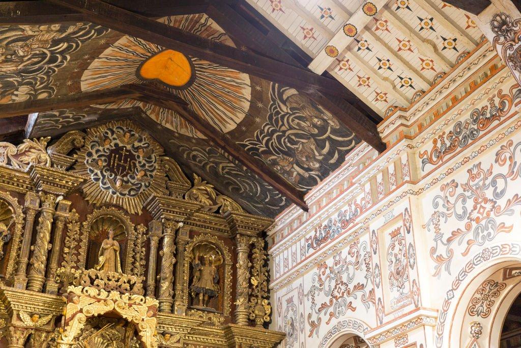 pinturas religiosas en el techo muestran un símbolo del sol dentro de la nave de la reducción jesuita en San Miguel.