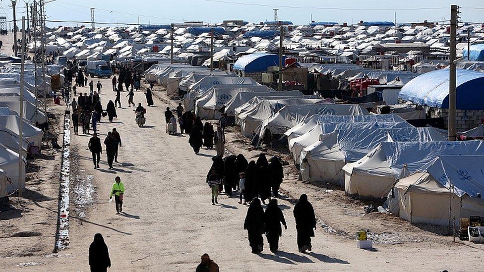 Mujeres caminan en el campamento de desplazados en al-Hawl, Siria, abril 1 de 2019