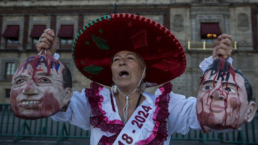 Una mujer sostiene máscaras de Calderón y Peña Nieto