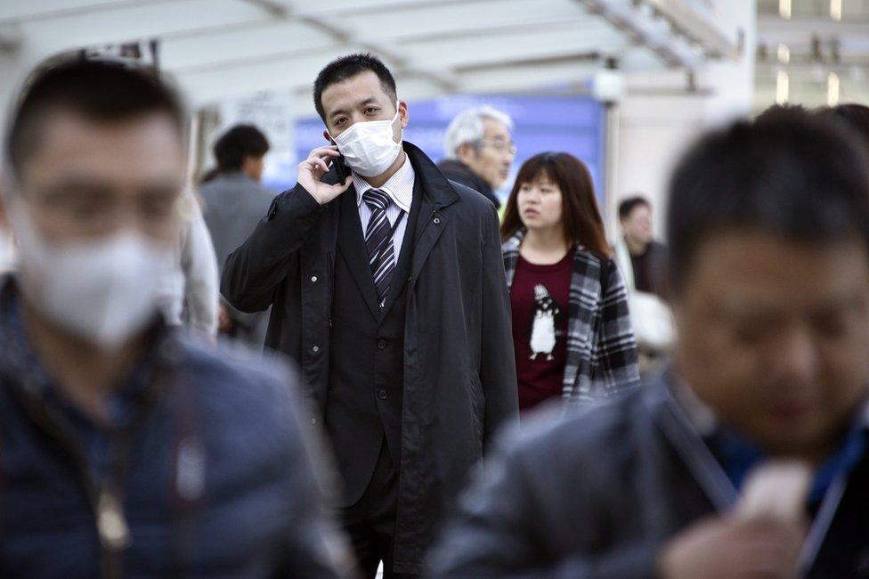 A man walks wearing a mask in Yokohama, near Tokyo, Japan, 26 February 2016