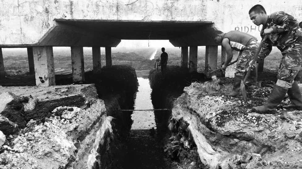 Soldiers in Kalimantan dig alongside a canal