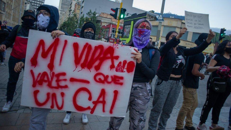 Manifestantes protestan con un cartel en contra de un CAI.