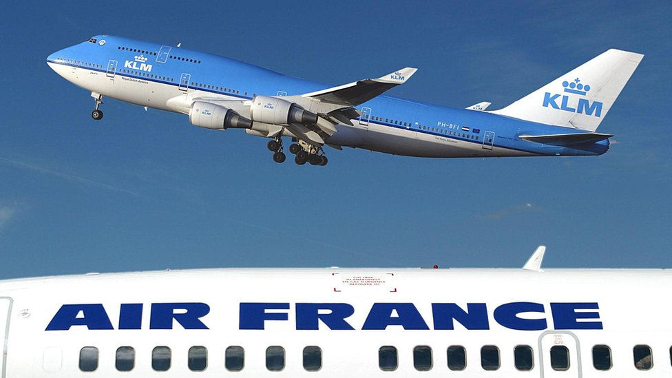 The top of one airplane, emblazoned with AIR FRANCE, occupies the lower third of this photo, while a blue KLM plane soars above it