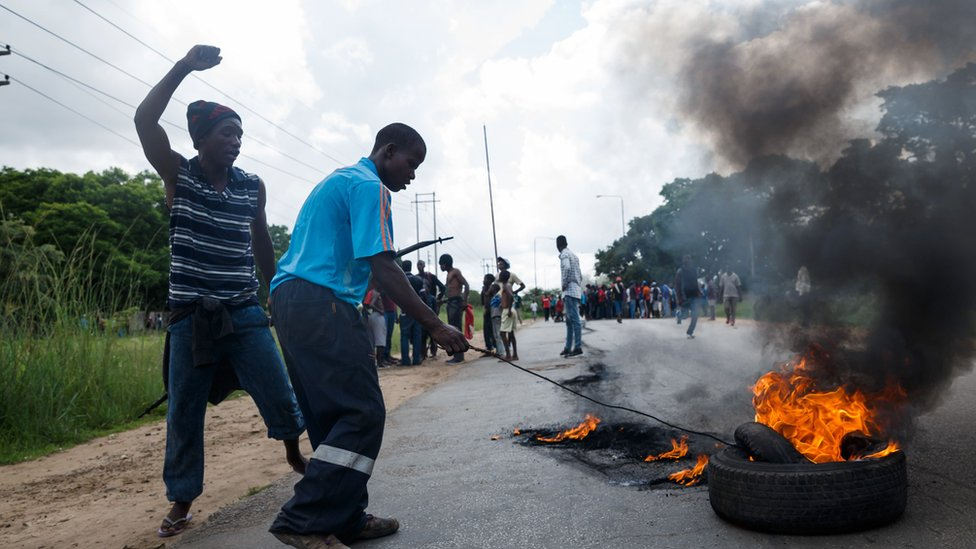 A man sets tyre on fire as angry protesters barricade the main route to Zimbabwe's capital Harare from Epworth township
