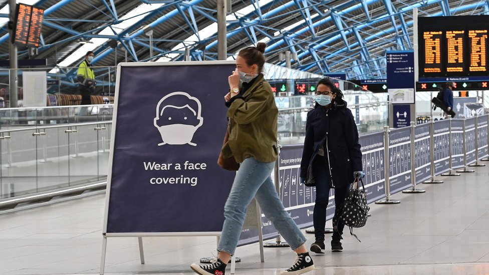 """A sign tells passengers to """"wear a face covering"""" at Waterloo train station in central London"""