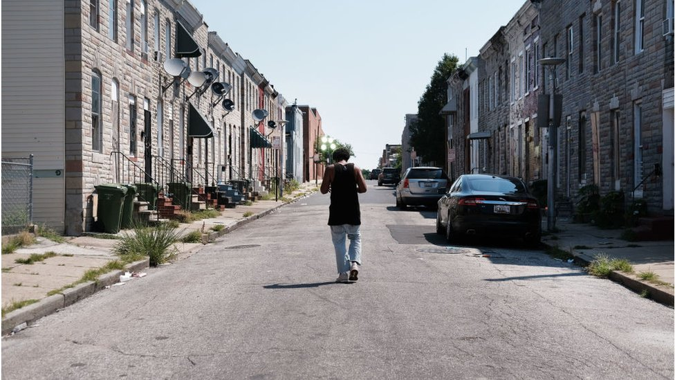A man walks down a Baltimore street near where a person was recently murdered on July 28, 2019 in Baltimore, Maryland
