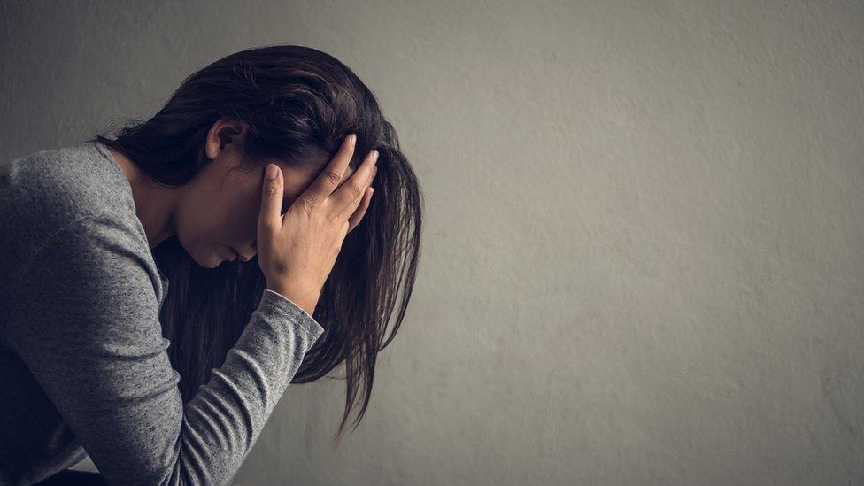 Mujer preocupada agarrándose la cabeza.
