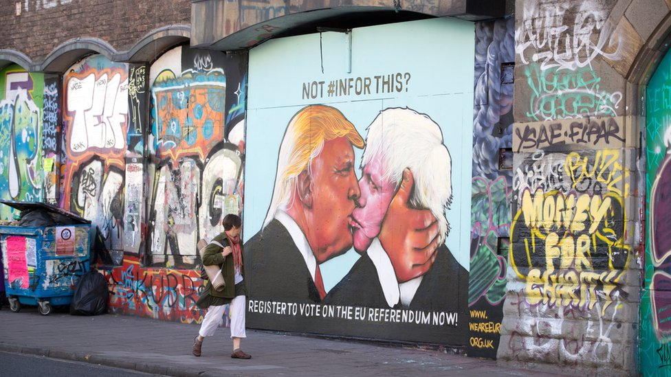 Donald Trump and Boris Johnson embrace depicted in Bristol street art