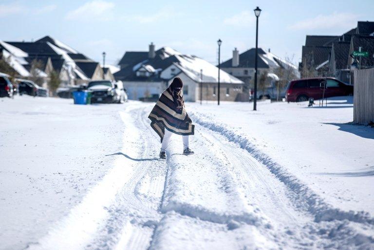 Una persona cruza caminando en una calle totalmente cubierta de nieve.
