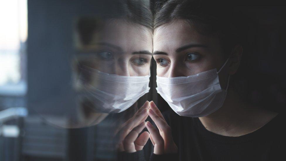 Mulher jovem com máscara olha pela janela