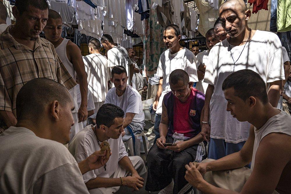 Inmates play cards while others watch, at the Chalatenango Penal Center, El Salvador. November 7, 2018.