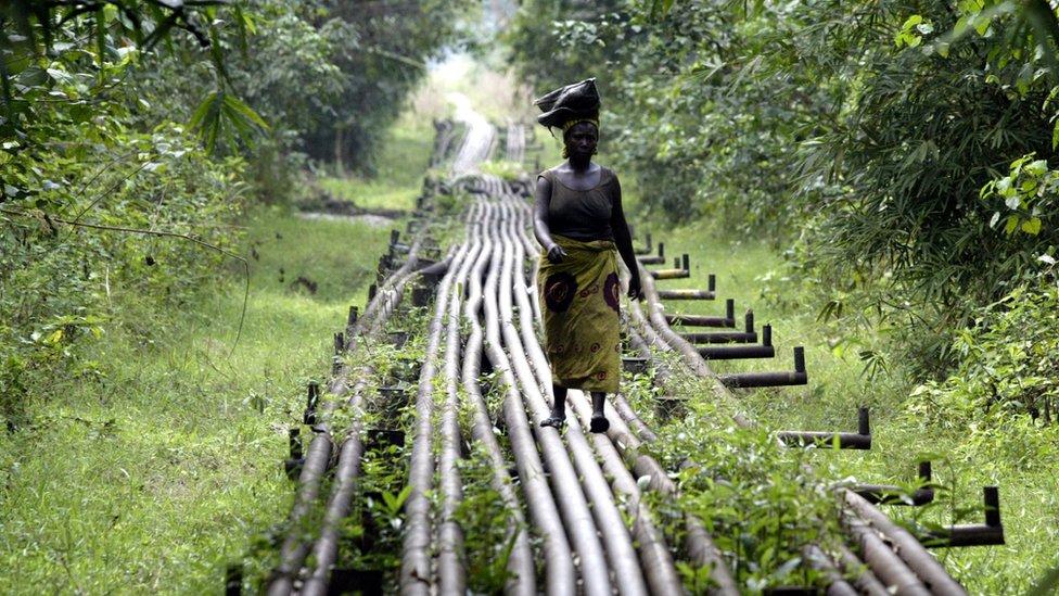 A woman walks along an oil pipeline in Warri, Nigeria