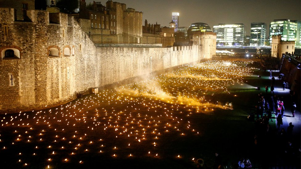 """The moat of the Tower of London are seen filled with thousands of lit torches as part of the installation """"Beyond the Deepening Shadow"""", in London,"""