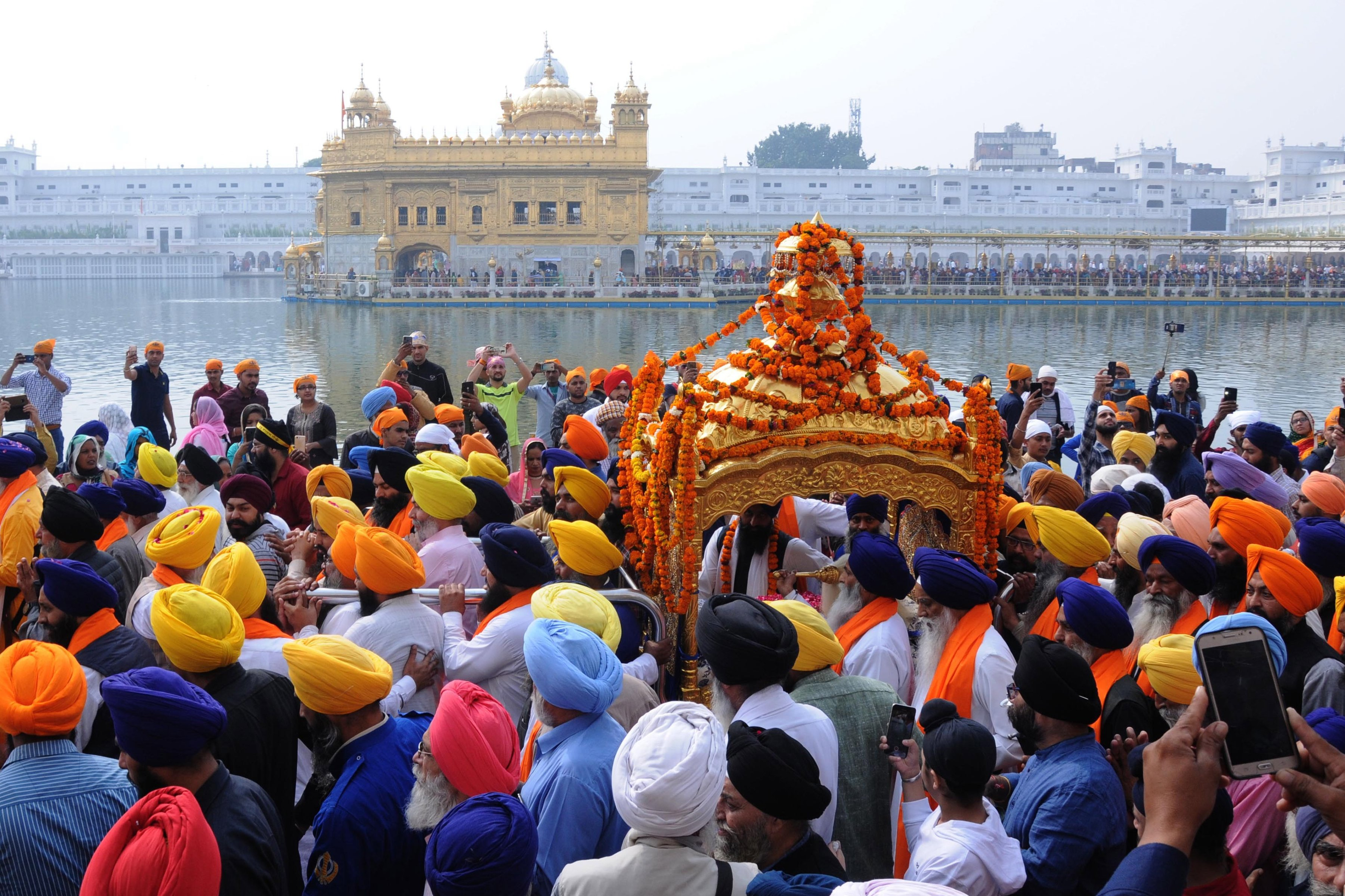 Sikh devotees carrying the Sri Guru Granth Sahib ji - the holy book of Sikh religion - in a hand-held, golden carriage