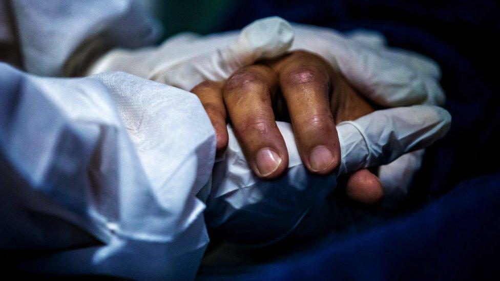 Un trabajador de la salud con equipo de protección personal toma la mano de un paciente en un hospital en Maricá, Brasil, abril 2021