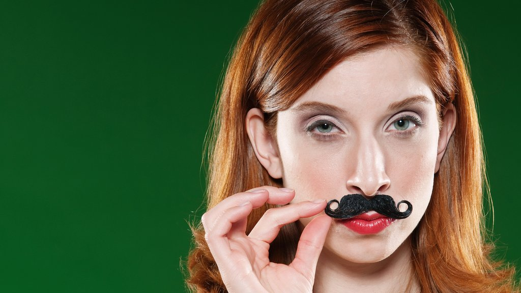 Chica poniéndose bigote postizo