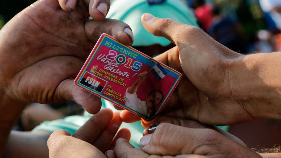 Antiguos simpatizantes sandinistas tratan de quemar su carnet de militantes del FSLN.