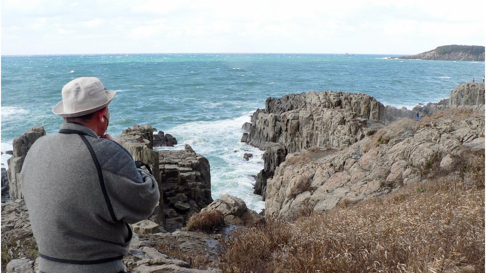 Former police officer Yukio Shige stands near the cliffs of Tojinbo, looking out to sea with a pair of binocular in hand. Fukui prefecture, northern Japan, 23 December 2008.