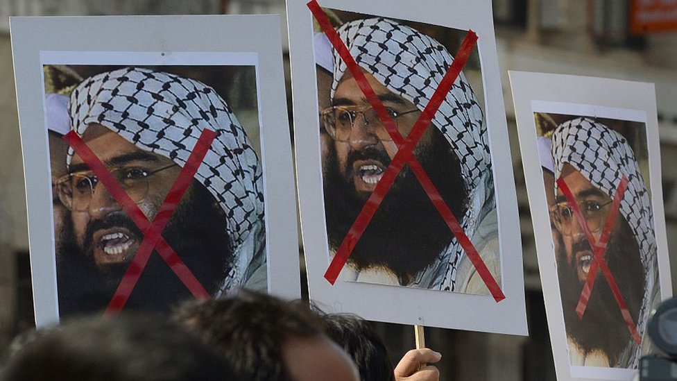 People protest carrying placards of Maulana Masood Azhar