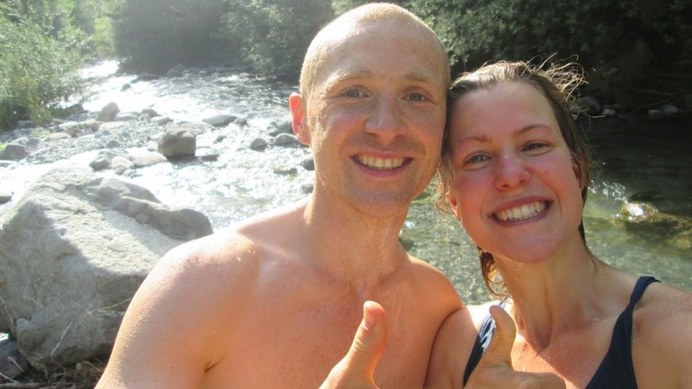 Dan and Esther give up a thumbs up after swimming in a river
