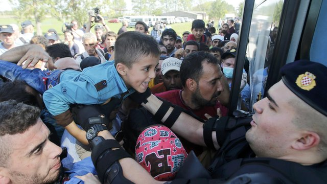 A policeman helps a boy as people board a bus in Croatia