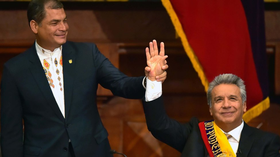 Ecuadorean outgoing President Rafael Correa (L) raises Ecuadorean new President Lenin Moreno's hand at the National Assembly in Quito on 24 May 2017, during Mr Moreno's inauguration ceremony