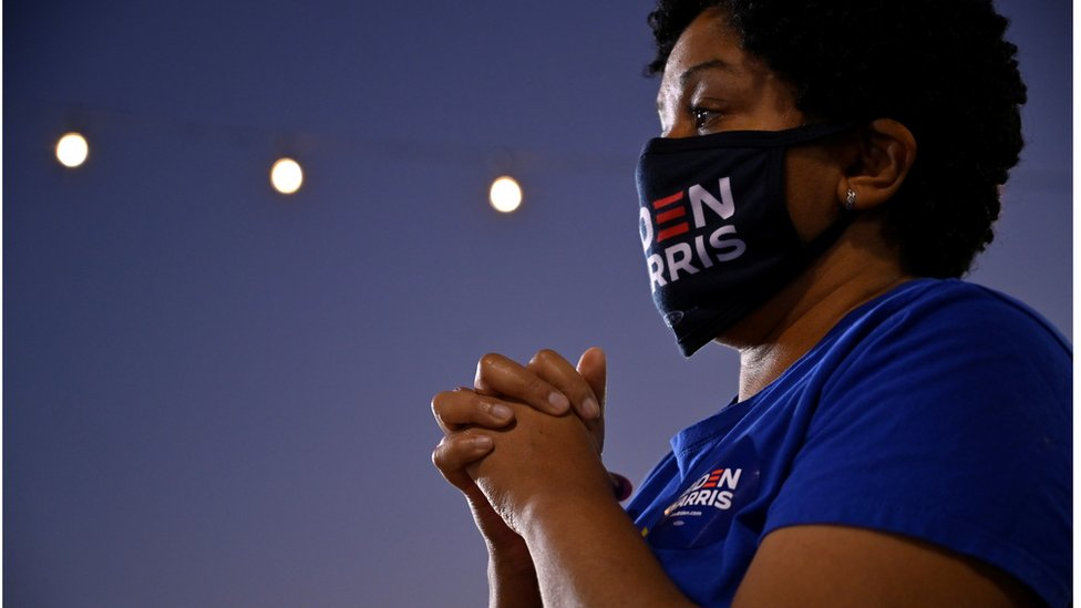 A democratic supporter with her hands clasped in prayer watches Senator Kamala Harris speaking in Las Vegas