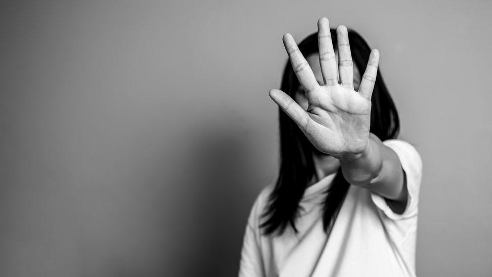 Una mujer con la mano tapándole el rostro