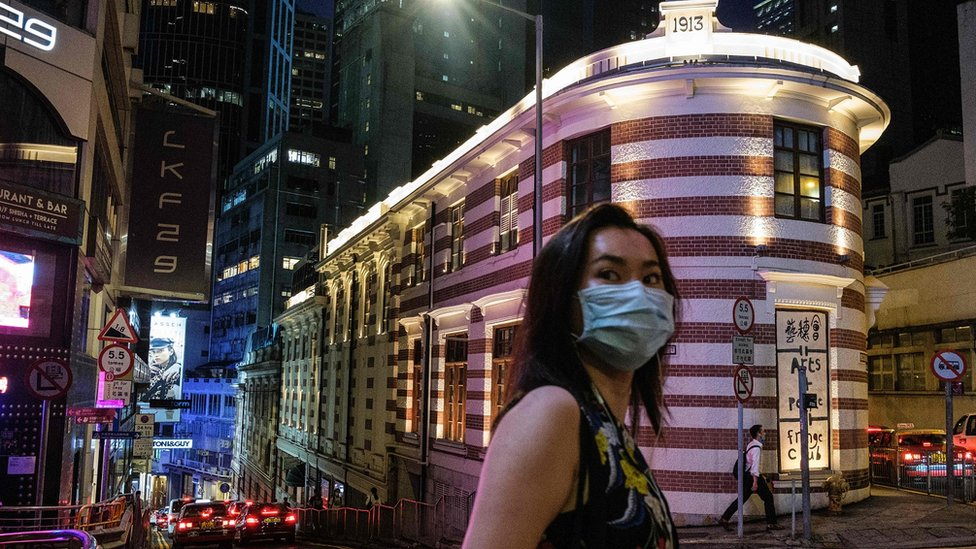 A woman walks past the Fringe Club (back C) building, which is housed in a Grade-I heritage building, the old Dairy farm cold storage depot, built circa 1892 and expanded in 1913, in Hong Kong on May 29, 2020.