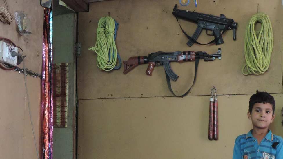The wall of a house in a refugee camp near Muzaffarabad with fake guns in the background (June 2015)