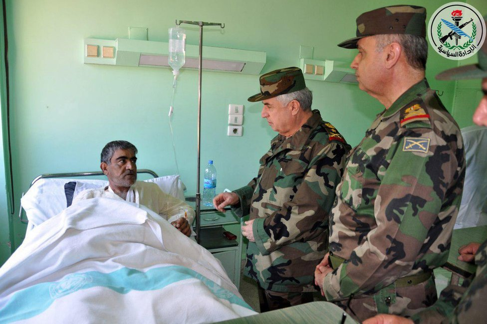 A handout photo made available by Syrian Arab news agency Sana shows Syrian Chief of the General Staff of the Army and Armed Forces Gen. Ali Abdullah Ayoub (C), visiting a Syrian pilot wounded in the US attack at Shayrat, 7 April