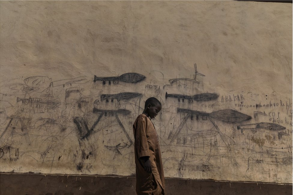 A child stands in front of wall covered in drawings