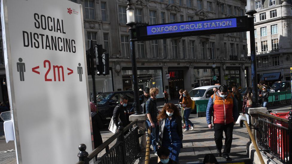 Travellers wear face masks as they enter Oxford Circus underground station