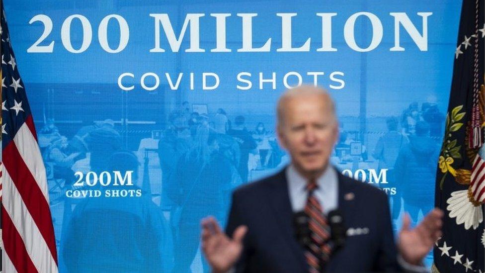 Biden faz discurso diante de painel em que se lê '200 milhões de doses aplicadas'