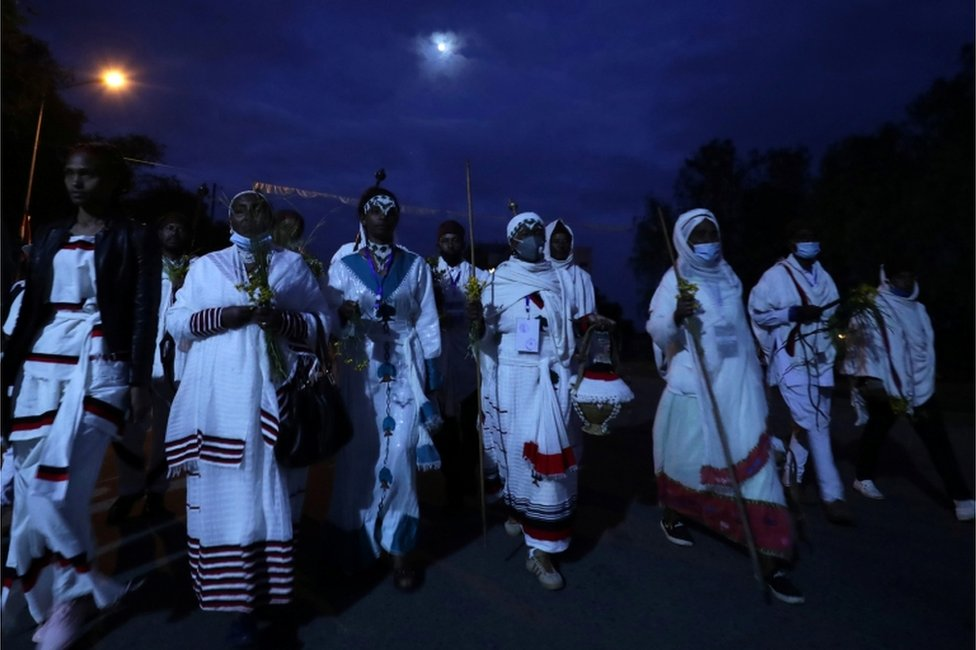Men and women dressed in white robes walk to attend Irreechaa celebrations.