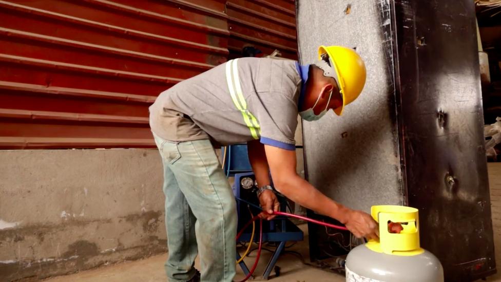 Un trabajador de la empresa de Ángel Toledo extrae gases refrigerantes de una nevera vieja.
