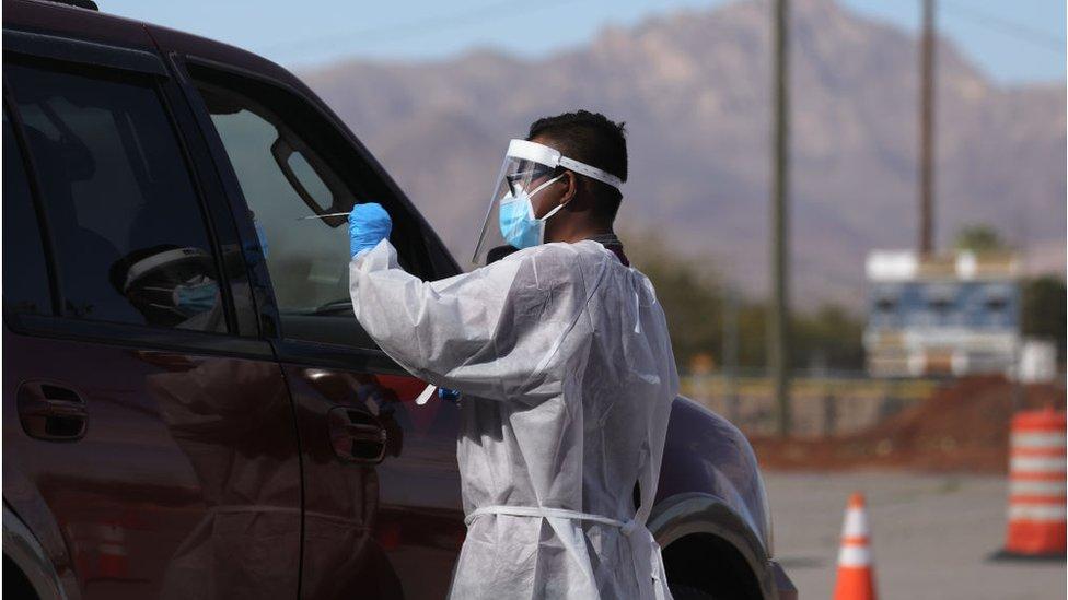 O profissional de saúde faz covid-19 em uma pessoa que está dentro de um carro