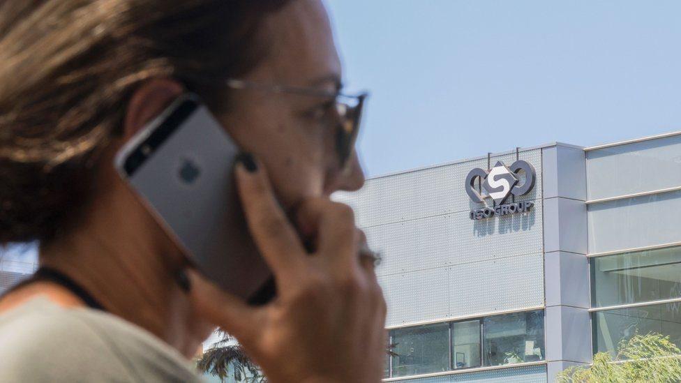 امرأة تستخدم هاتف أيفون من أمام شركة إن إس أو