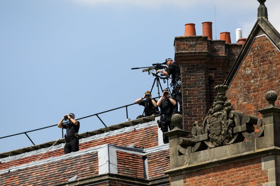 Armed British police officers look out from the roof of Chequers ahead of a joint news conference