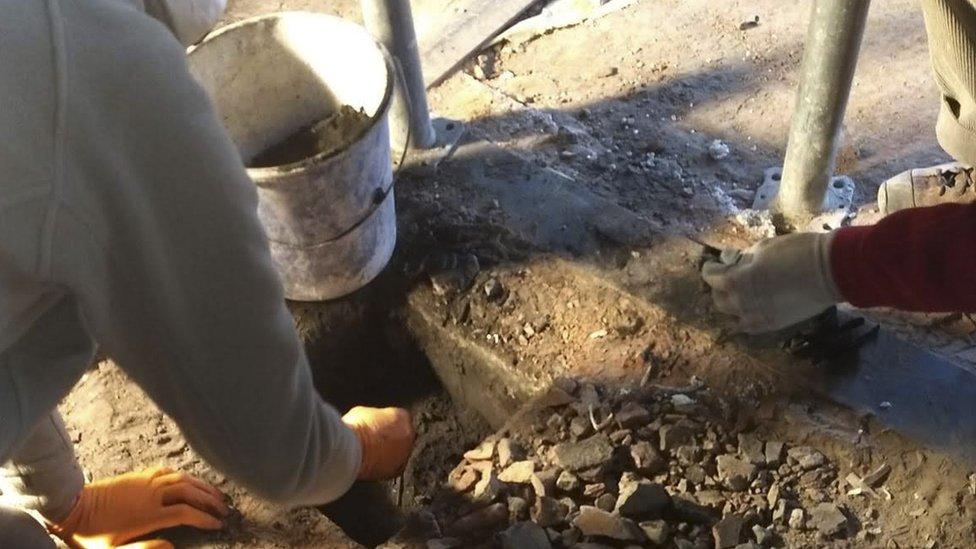 Los renovadores encuentran objetos escondidos debajo de una chimenea en Auschwitz.