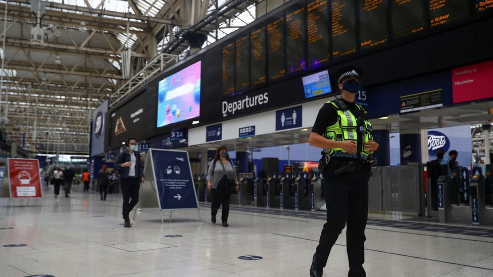 Police officer in face mask walks through empty Waterloo station
