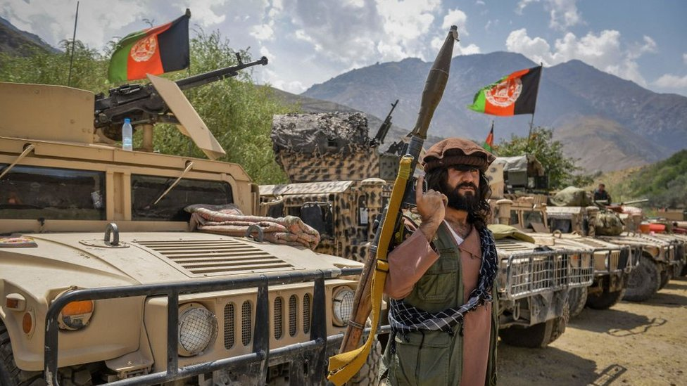 An Afghan soldier holds a rocket propelled grenade and stands in front of military vehicles