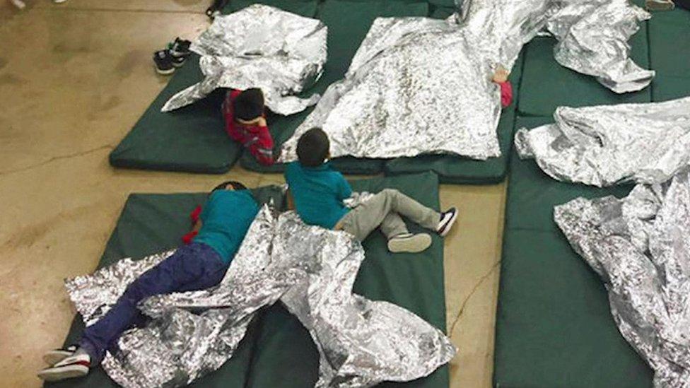 Tres niños se acuestan en delgados colchones verdes en el piso cubiertos con mantas de aluminio.