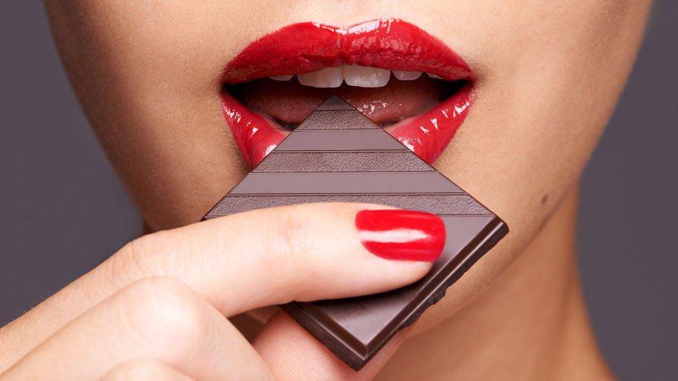 Ženske usne koje grckaju parče čokolade