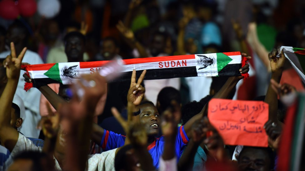 Sudanese protesters wave flags and flash victory signs as they gather for a sit-in outside the military headquarter