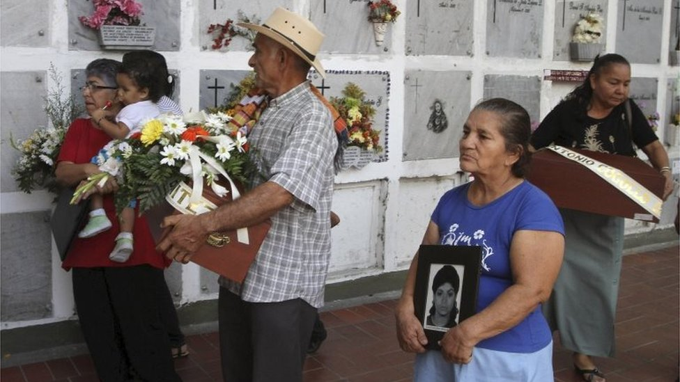 Leonel de Jesus Vargas carries a small coffin containing the remains of his daughter Gloria, as he is accompanied by his wife Rosa, in San Pedro cemetery in Medellin on 25 February, 2011
