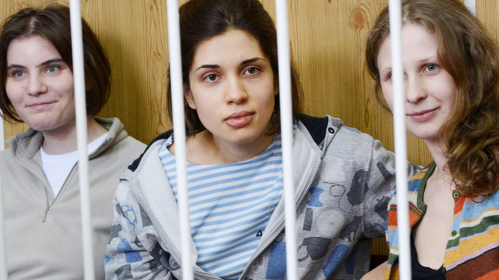 Members of the all-girl punk band 'Pussy Riot' Nadezhda Tolokonnikova (C), Maria Alyokhina (R) and Yekaterina Samutsevich (L), sit behind bars during a court hearing in Moscow in July 2012