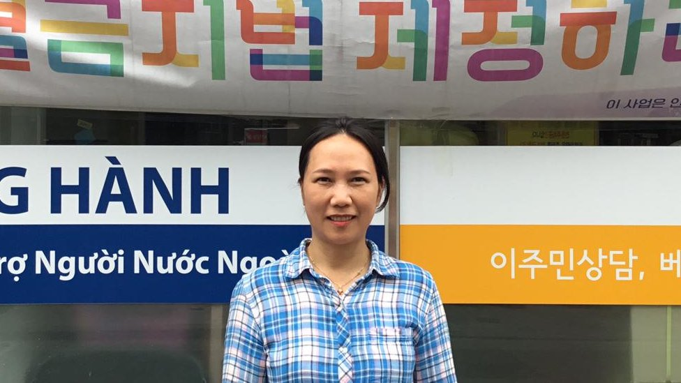 Won Ok Kum stands outside her office with Korean and Vietnamese signage on display.