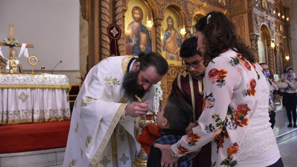 Dete se pričešćuje posle nedeljne mise u crkvi Svetog Elijasa u Alepu.